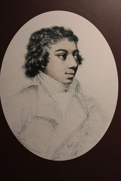 Side profile portrait of a mixed race man with short wavy hair. He is wering a cravat and jacket and looking into the distance with a faint smile.
