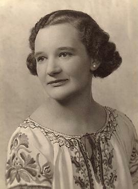 A woman with short 1920s waved hair looking into the distance. She is wearing a white blouse with flower embroidery and white pearl earrings.