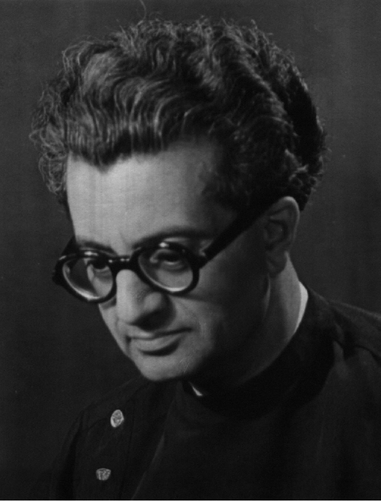 Photograph a man with dark wavy hair looking down. He is wearing a black jacket with round buttons and thick black rimmed glasses.
